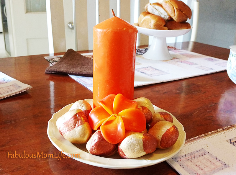 orange candle and painted stones centerpiece